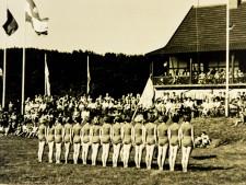 historische Aufnahme einer Gruppe von Frauen in Sportkleidung, die auf einer Wiese vor einem großen Publikum stehen