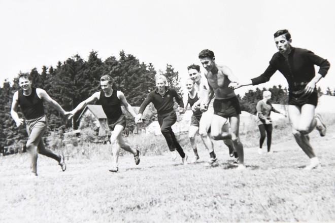 historische Aufnahme einer Gruppe junger Männer in Sportkleidung, die über die Wiese rennen