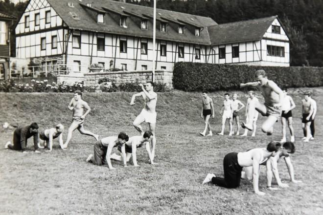 historische Aufnahme junger Sportler auf der Wiese, im Hintergrund ist ein Fachwerkhaus zu sehen