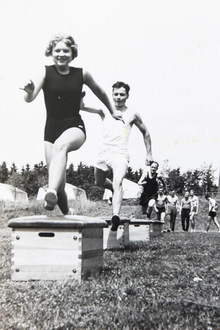 historische Aufnahme einer Gruppe von jungen Menschen in Sportkleidung, die über Sprungkästen springen