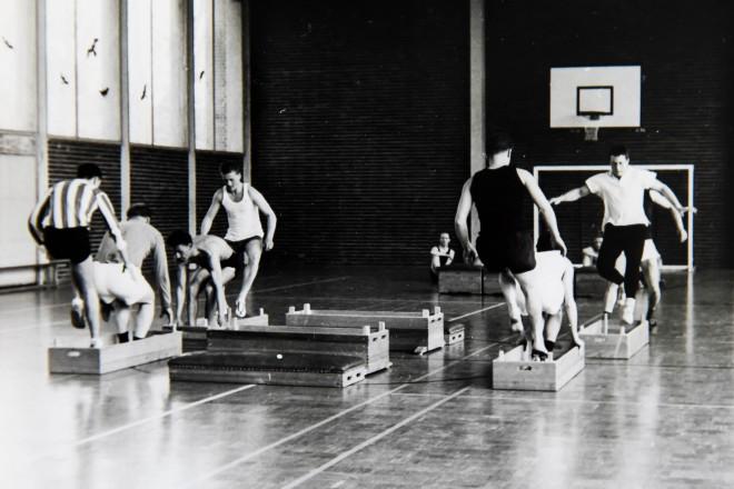 historische Aufnahme einer Gruppe von jungen Sportlern in der Turnhalle