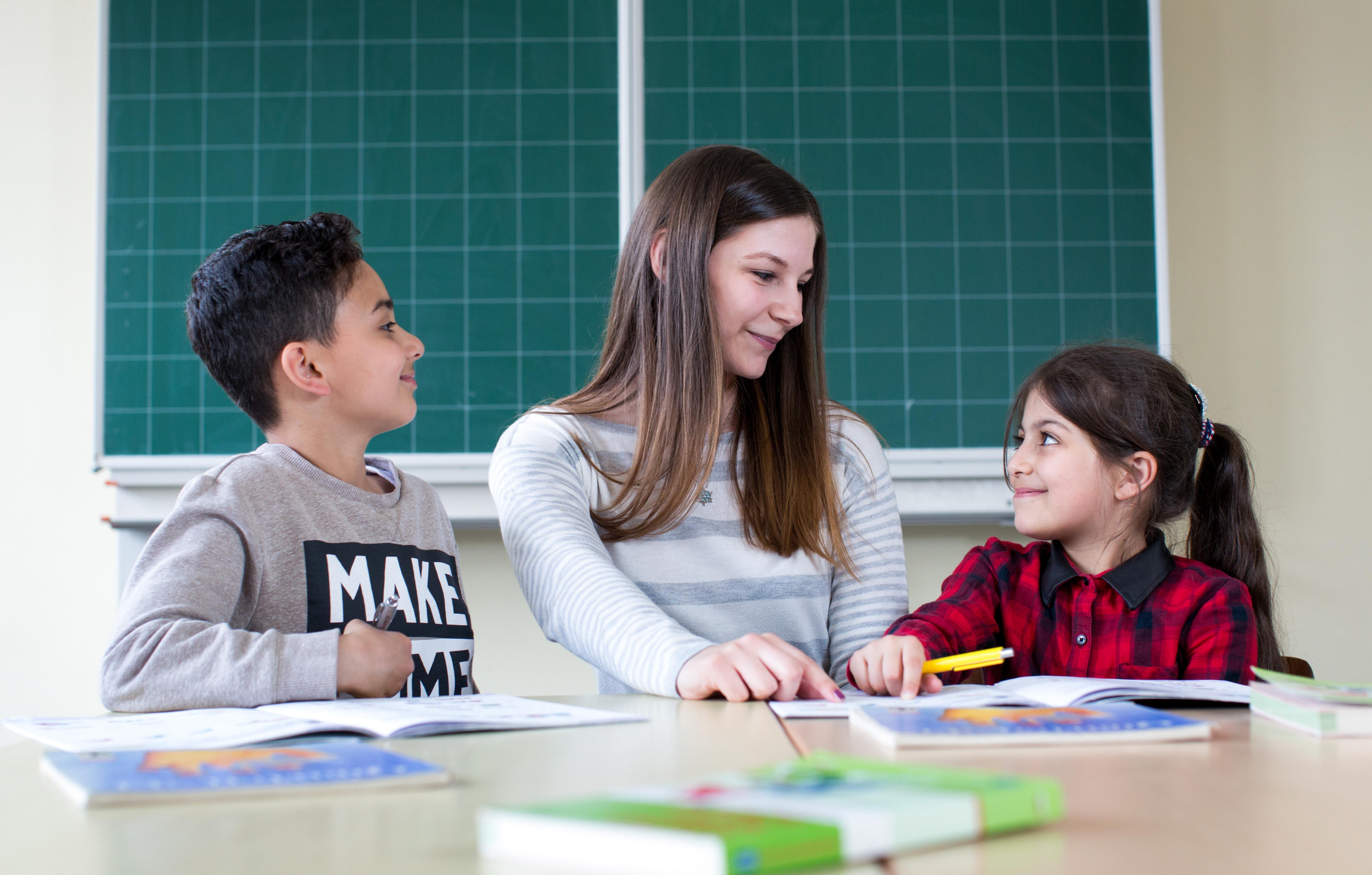 Eine junge Lehrerin sitzt zwischen einem kleinen Mädchen und einem Jungen, denen sie Nachhilfeunterricht gibt. Beide Kinder hören freudig gespannt zu.