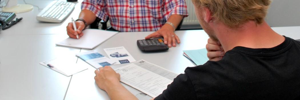 Ein Leistungssachbearbeiter und ein JobCenter-Kunde besprechen am Schreibtisch die Anspruchsvoraussetzungen des Kunden