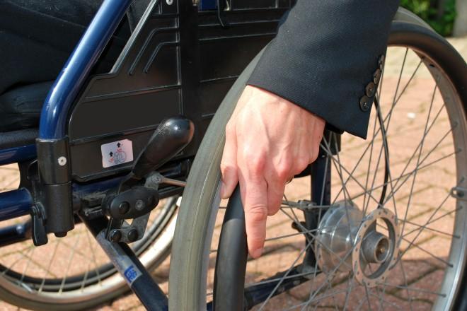 Eine Hand treibt das Rad eines Rollstuhls an