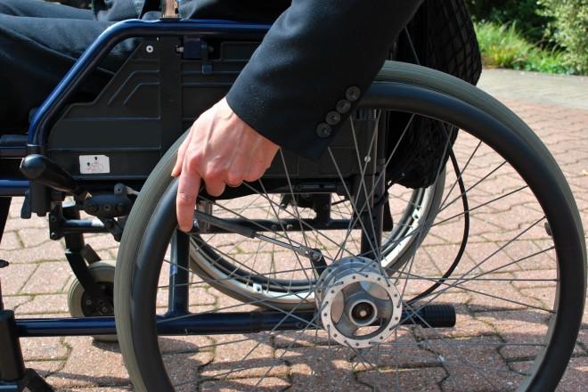 Eine Hand treibt das Schwungrad eines Rollstuhls an.