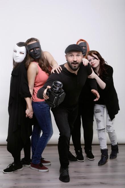 Maskiertte Frauen umringen einen Mann mit Kamera. Die Szene ist freundlich, fast zärlich.