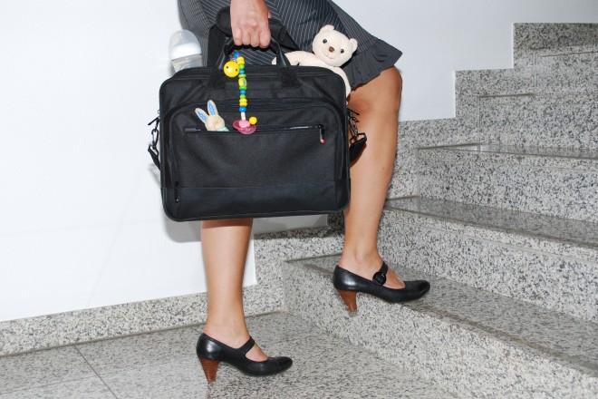 Eine Frau steigt eine Bürotreppe hinauf, in ihrem Laptop-Koffer stecken auch Teddybäre, Schnuller und Babyfläschen.