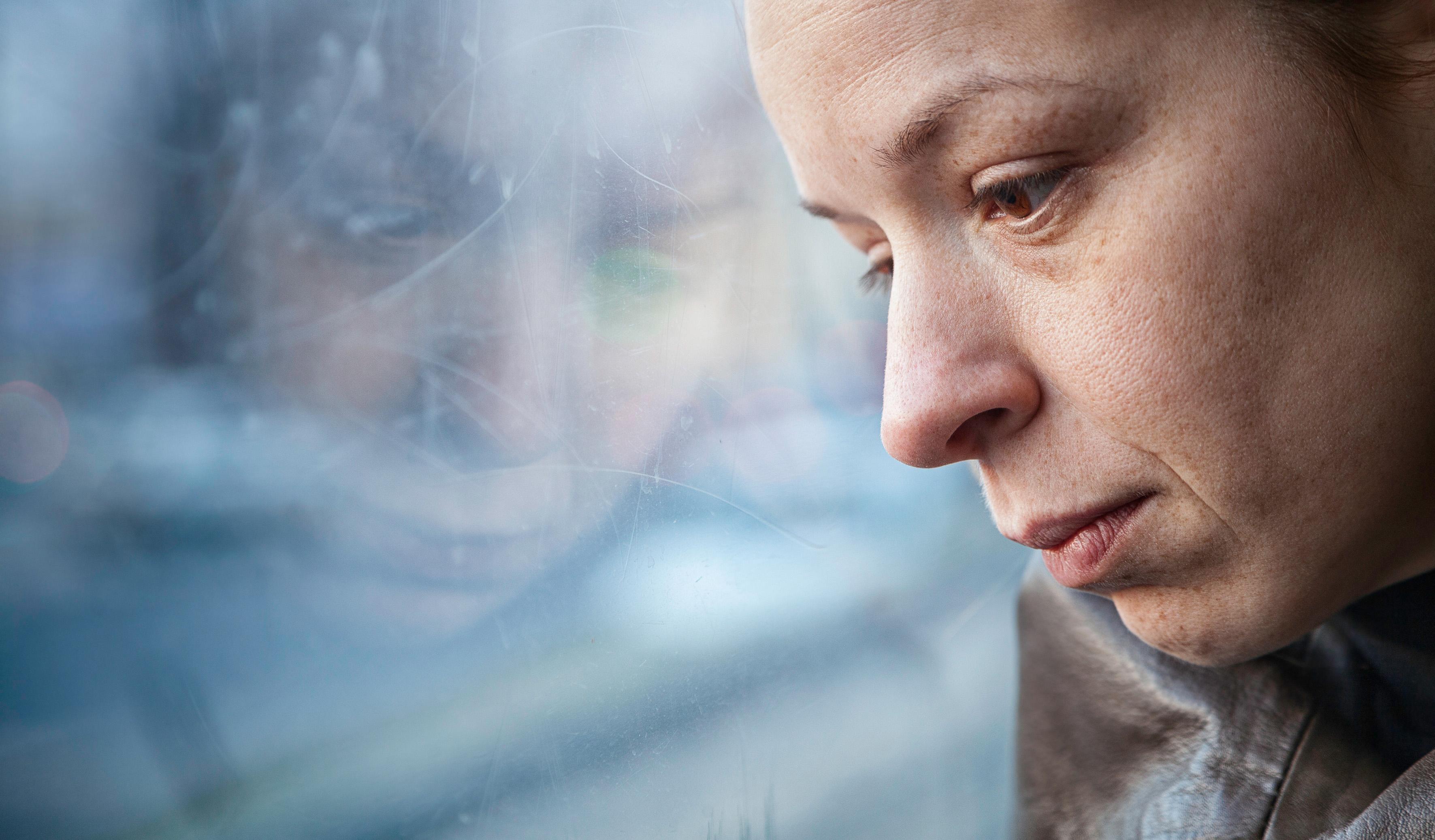 Nachdenkliche Frau aus dem Fenster schauend