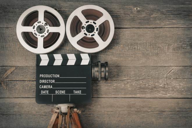 Das Foto zeigt Filmrollen, Regieklappe, Filmkamera und Stativ vor einer groben Holzwand.
