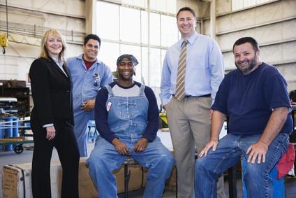 Eine Arbeitsvermittlerin, mehrere Arbeitssuchende und ein Arbeitgeber in einer Werkhalle, alle Personen lächeln zufrieden.