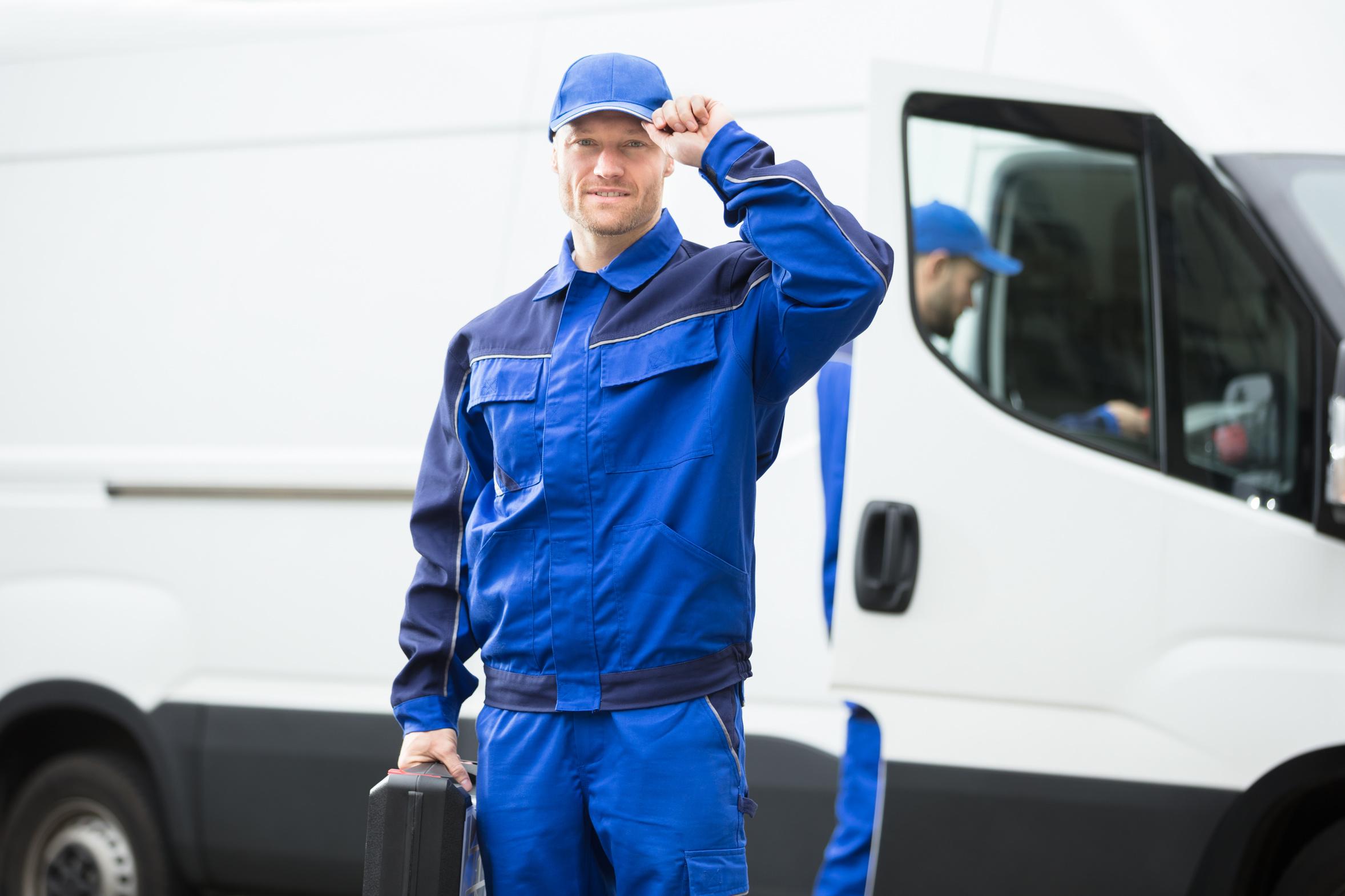 Ein Mann in dunkler Arbeitsjacke fasst sich grüßend an seine Schirmmütze. Im Hintergrund steht ein zweiter Monteur an einem geöffneten Kleintransporter.