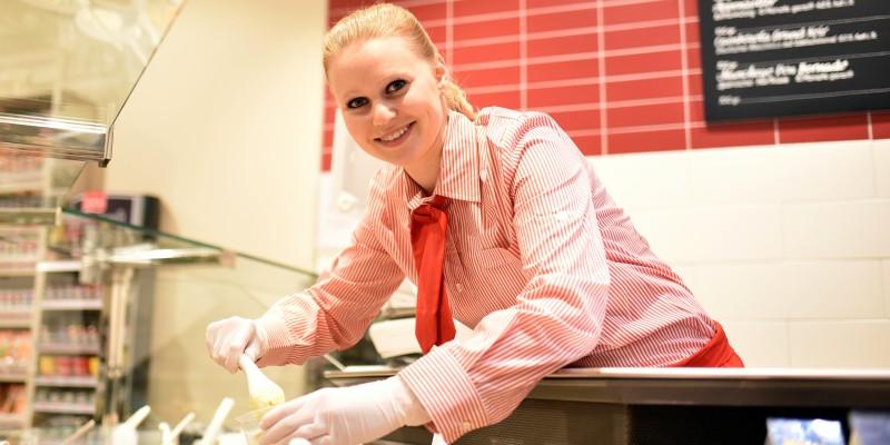 Im Supermarkt: Eine junge rothaarige Frau in rot-weiß gestreifter Dienstkleidung beugt sich über eine Kühltheke und füllt mit einem Löffel portionsweise Antipasti ab.