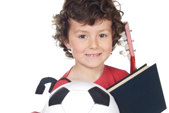 Glücklich lächelndes Kind mit Fußball, Rucksack, Buch und Gitarre