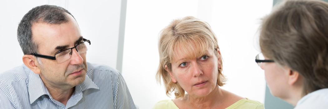 Ein Mann und eine Frau mittleren Alters hören einer zweiten Frau am rechten Bildrand aufmerksam bei einer Erklärung zu.
