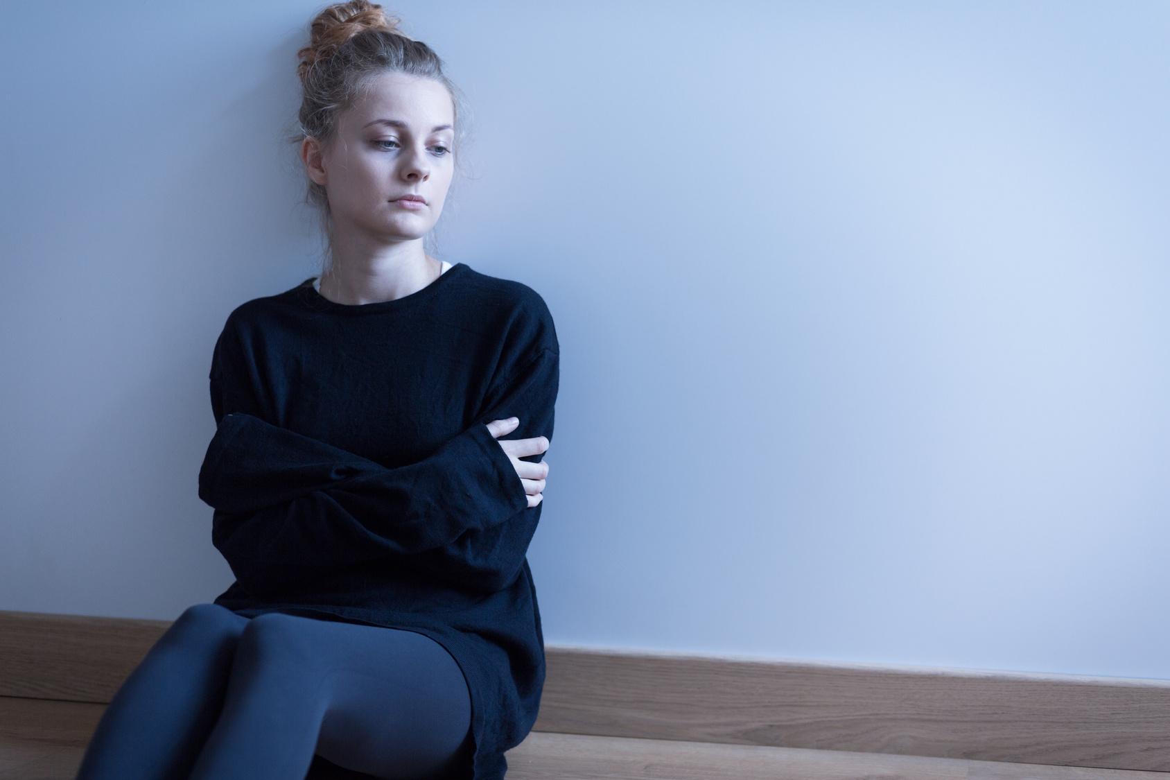Trauriges Mädchen am Boden sitzend