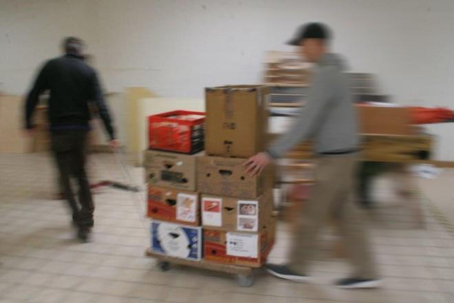 Zwei Männer bewegen viele auf einem Wagen gestapelte Kisten schnell durch eine Langerhalle. Wegen der Eile ihrer Bewegung sind sie nur unscharf zu erkennen.