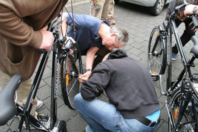 Mehrere Männer beugen sich über ein Fahrrad um die Vorderradnabe zu reparieren.