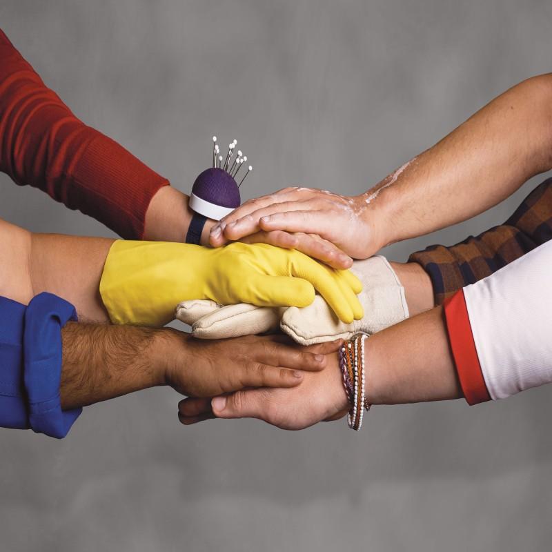 Hände, die durch Attribute wie Arbeitshandschuhe u.ä. verschiedene Tätigkeiten und Berufe repräsentieren, treffen sich in der Mitte des Bildes.