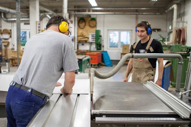 Ein Auszubildender und sein Ausbilder arbeiten an einer mechanischen Säge