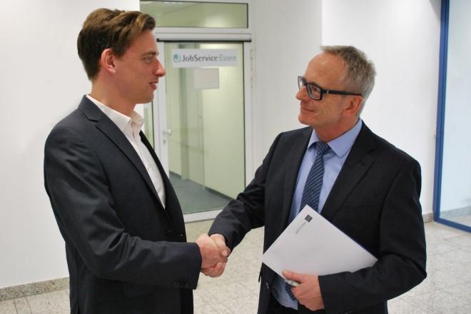 Zwei Männer tauschen in einem Bürofoyer einen Handschlag aus. Sie besiegeln damit eine Einstellung.