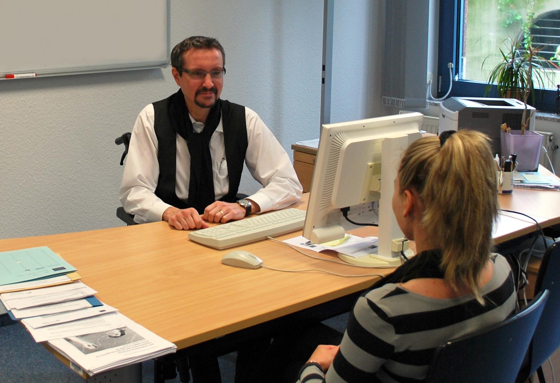 Ein Arbeitsvermittler und eine Arbeitssuchende sitzen sich am Schreibtisch gegenüber und beraten die beruflichen Perspektiven der Kundin.