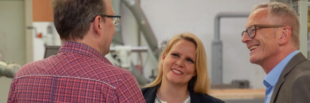 Ein Mitarbeiterin und ein Mitarbeiter des JobService Essen sprechen mit einem Arbeitgeber in seiner Werkstatt über seine Personalsituation