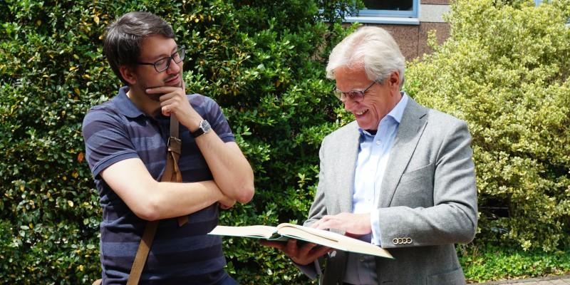 Zwei Personen schauen gemeinsam in ein Buch