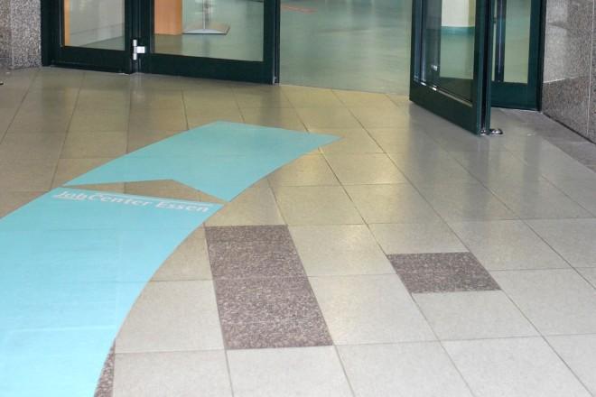 Das Bild zeigt einen Eingang vom JobCenter Essen. Eine geschwungene Bodenmarkierung zeigt der / dem Besucher*in den Weg