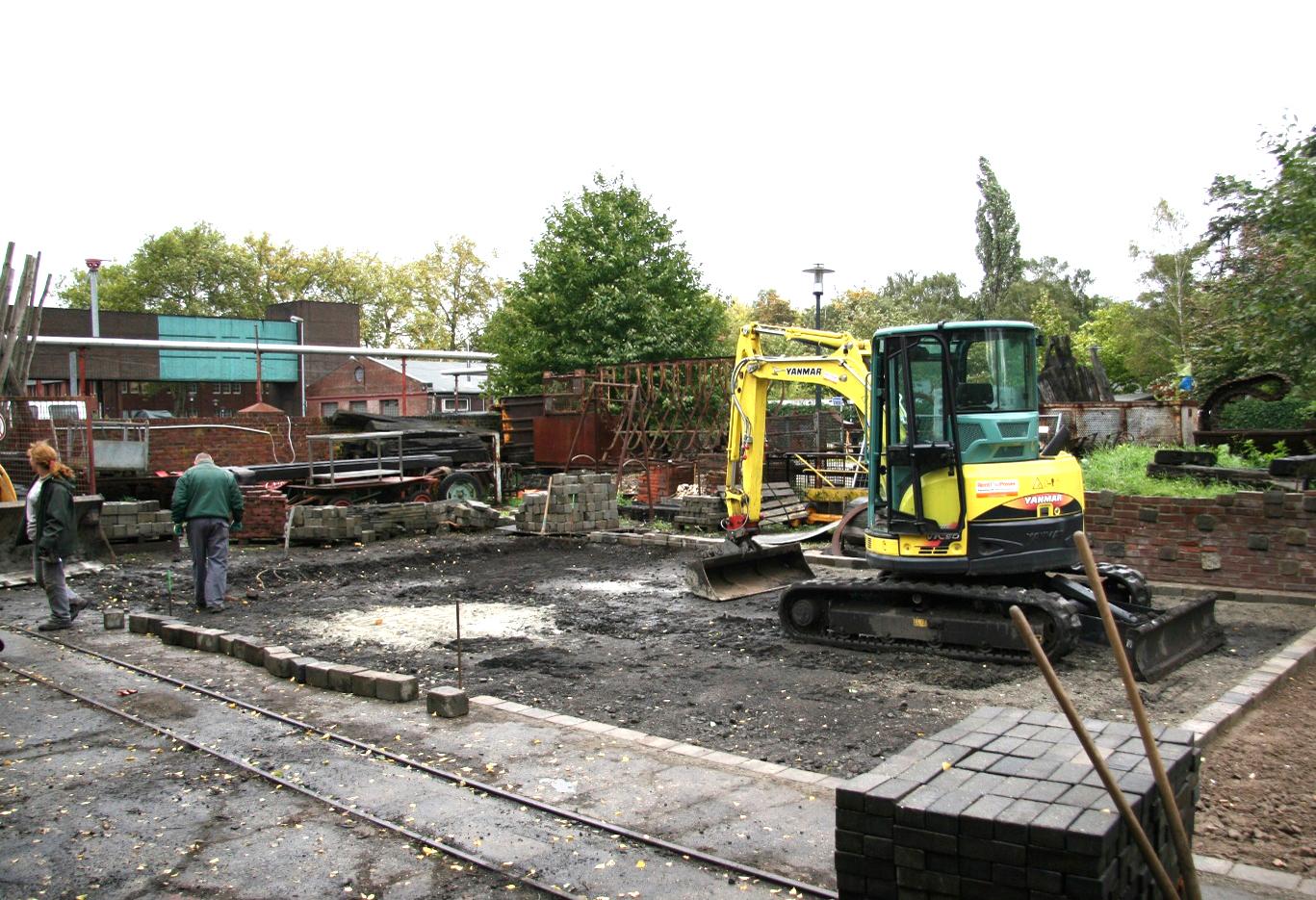 Eine Fläche wird mit einem Bagger geebnet. Steine für die nachfolgende Pflasterung liegen bereit.