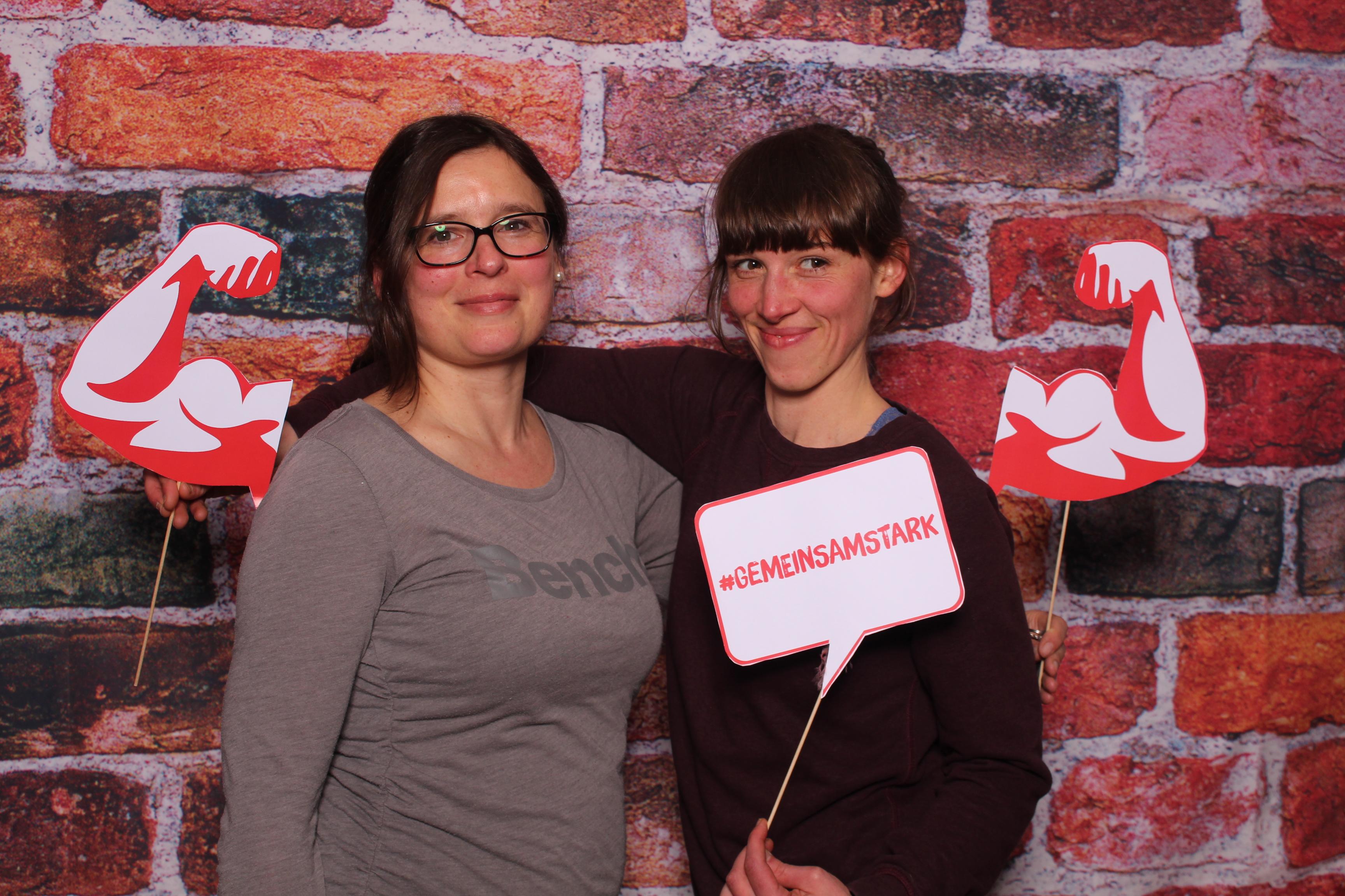 """Zwei Mitarbeiterinnen des Verbandes mit einem Schild, das die Aufschrift """"Gemeinsam stark!"""" trägt"""
