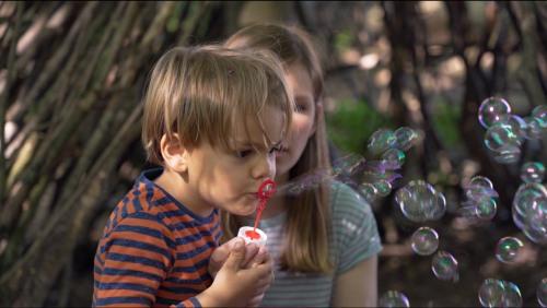 Zwei Kinder mit einem Seifenblasenspiel