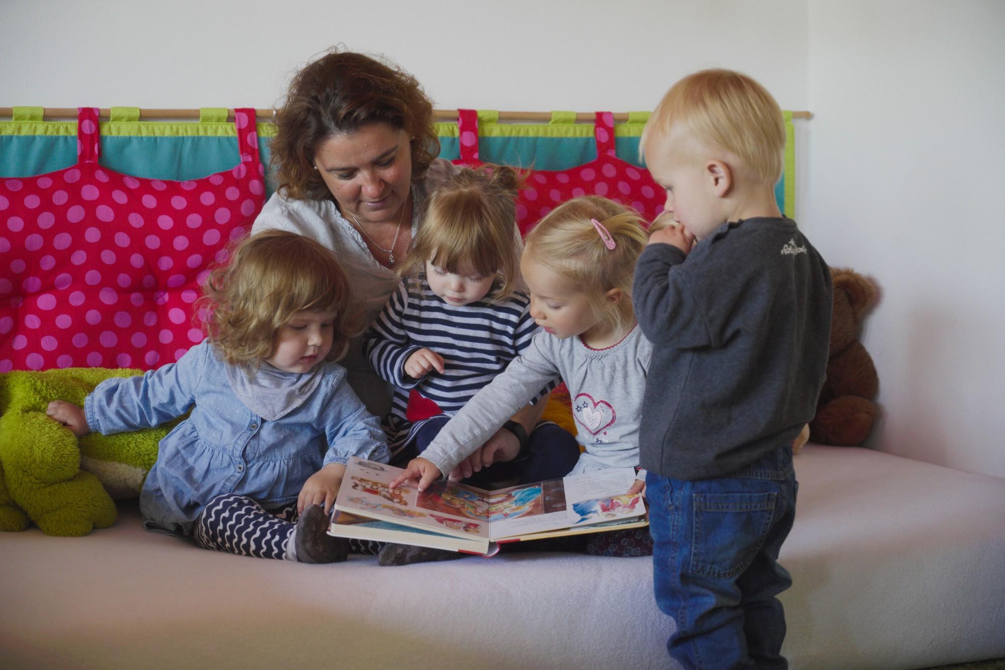 Tagesmutter schaut mit vier Kindern ein Buch an
