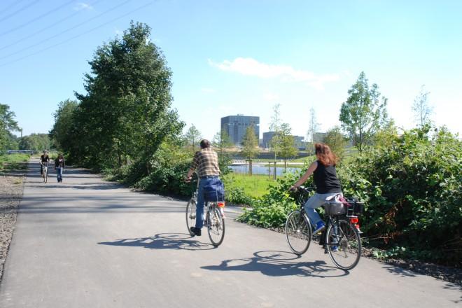 Radweg mit Fahrradfahrern und ThyssenKrupp-Hauptzentrale im Hintergrund