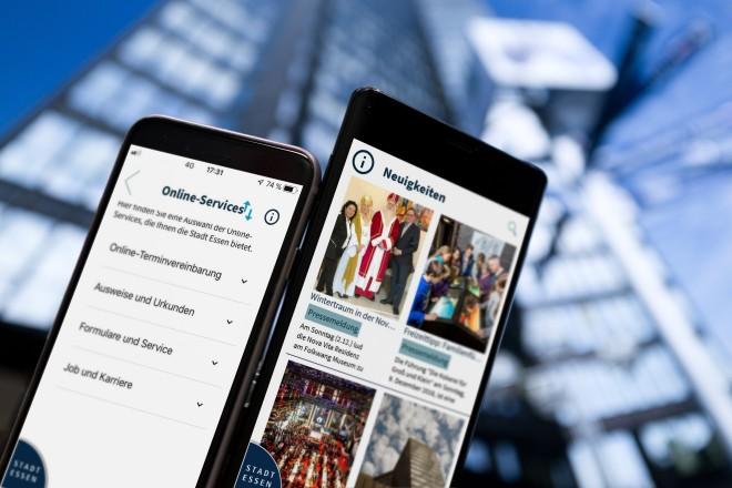 Zwei Smartphones zeigen auf Ihren Bildschirmseiten das Stadtportal Essen to go App. Hinter ihnen sieht man unscharf das Essener Rathausgebäude