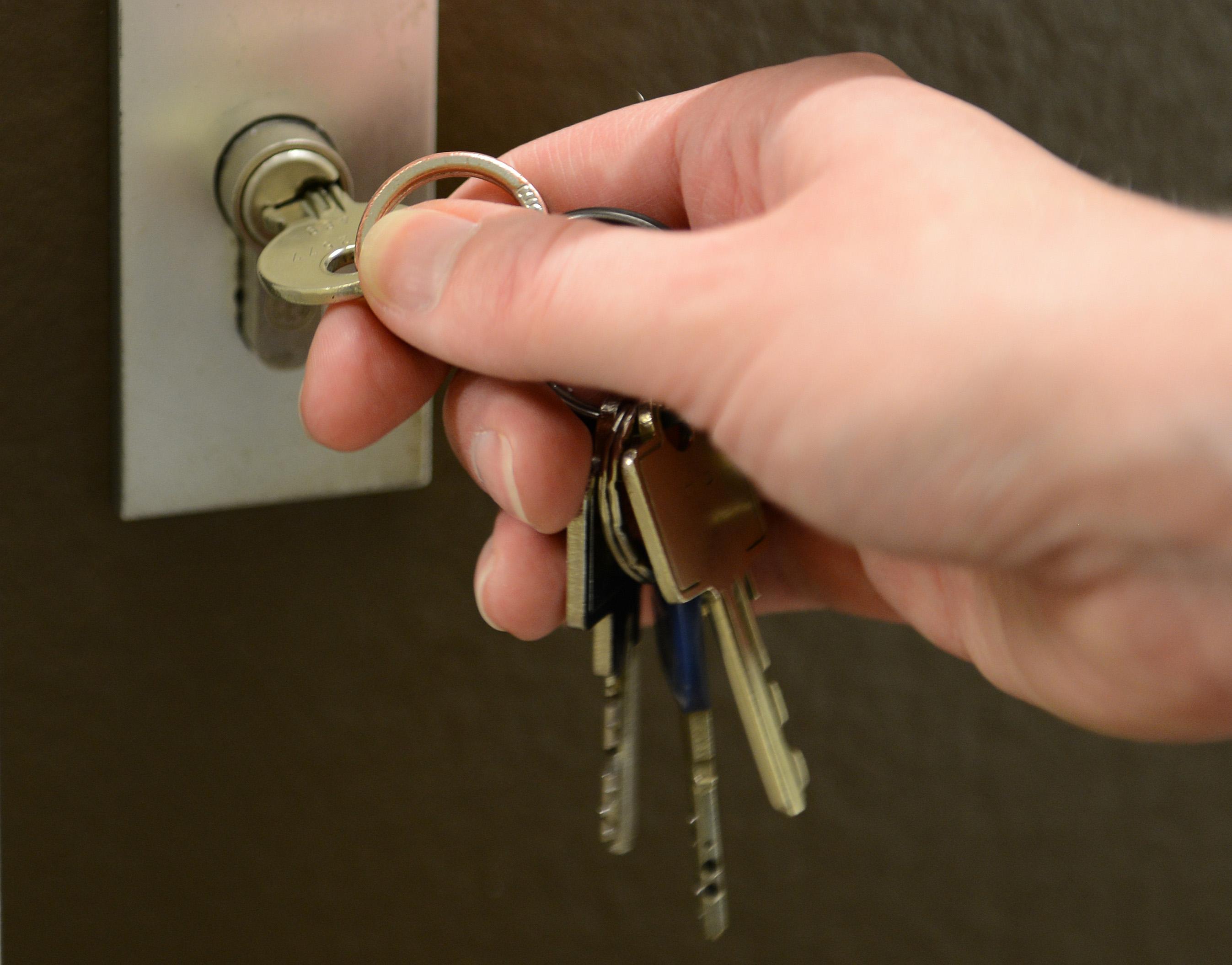 Foto mit einer Hand, die einen Schlüssel in ein Türschloss steckt