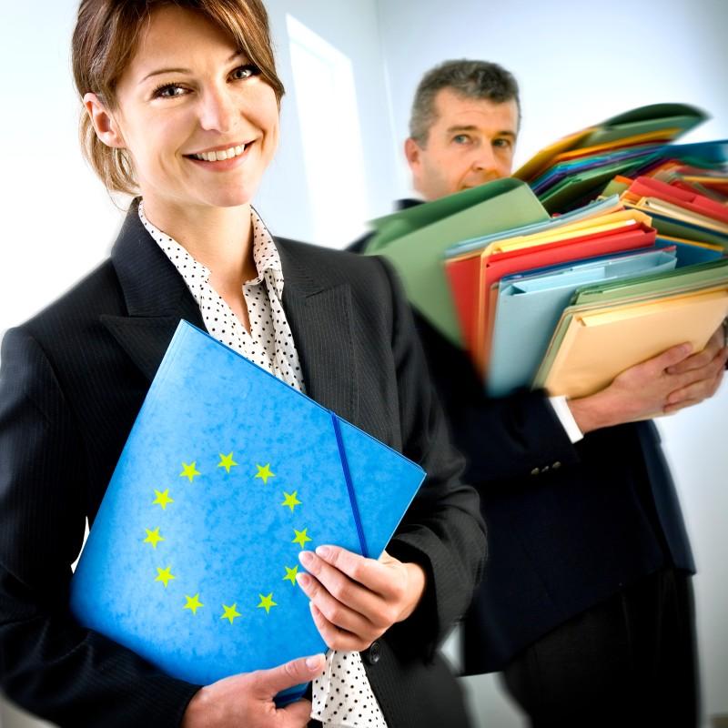 Foto: lächelnde Frau mit Handmappe, im Hintergrund: Mann mit vielen Akten