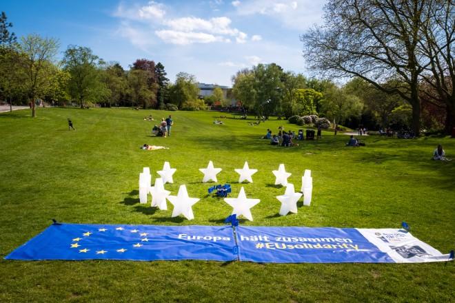 Foto:12 leuchtende Sterne im Kreis angeordnet, auf einer Wiese stehend, davor EU-Banner
