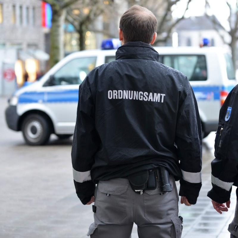 Foto: zwei ältere Männer schauen auf ein Polizeiauto