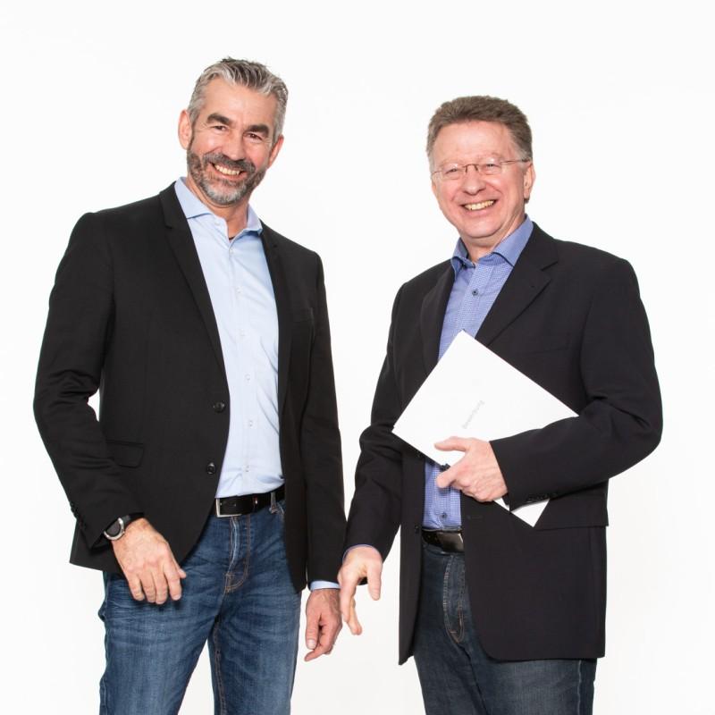 Zwei Männer bei der Übergabe einer Bewerbung