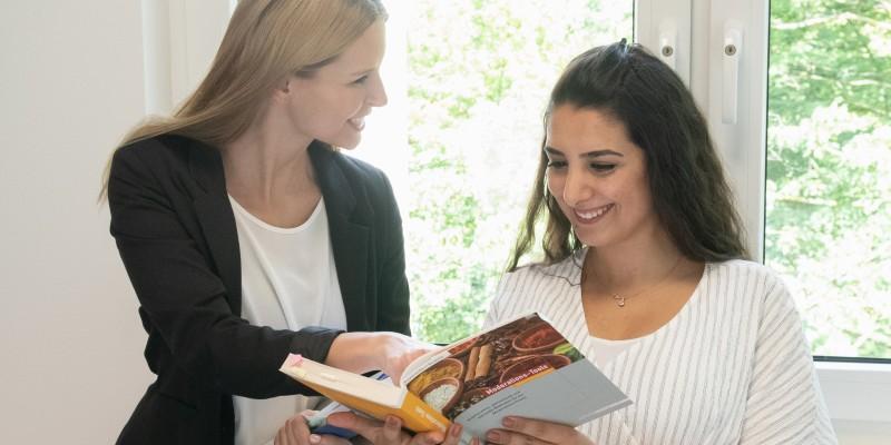 Foto: zwei lächelnde Frauen schauen gemeinsam in ein Buch
