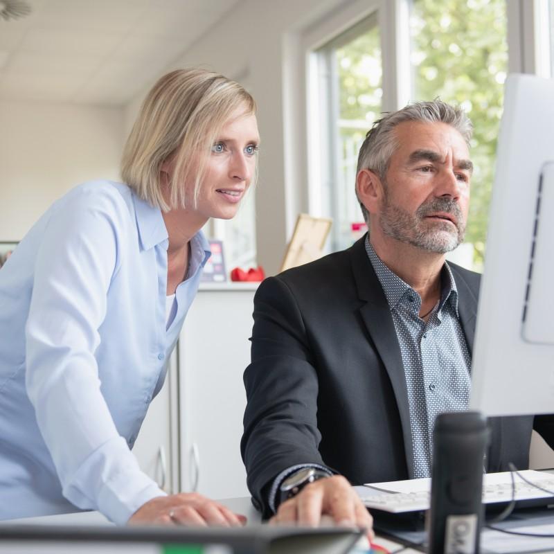 Foto: Eine Frau die einem Mann am PC etwas erklärt