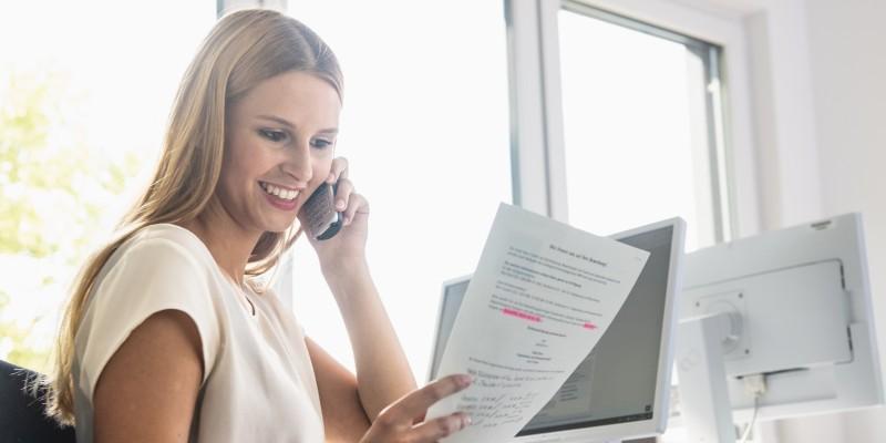 Foto: eine junge lächelnde Dame sitzt an einem Schreibtisch mit einem Telefon und einem Schriftstück in der Hand