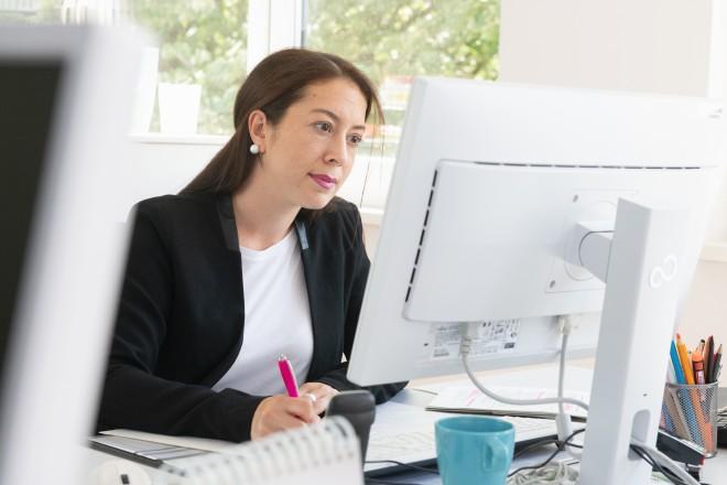 Auszubildende macht sich Notizen vor dem Bildschirm