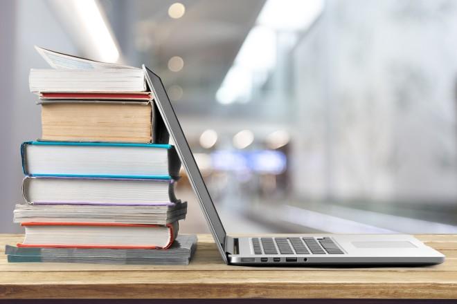 Bücherstapel und Laptop