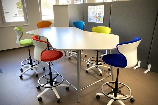 Es ist ein Besprechungstisch mit mehreren hohen Stühlen abgebildet.