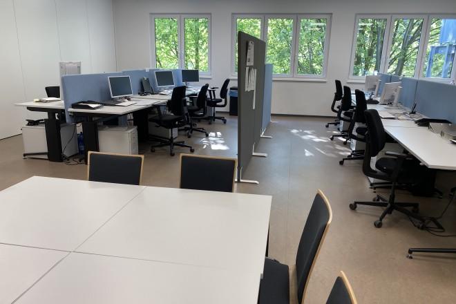 Es ist ein Büroraum mit mehreren Schreibtischen, Stühlen und IT Ausstattung abgebildet.