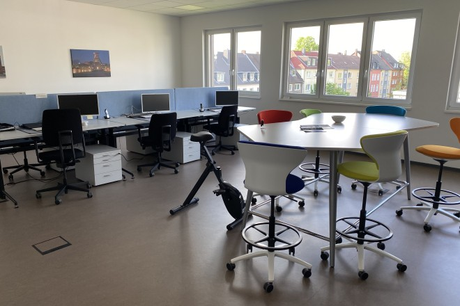 Es ist ein Büroraum abgebildet, indem sich ein hoher Besprechungstisch mit Stühlen befindet.