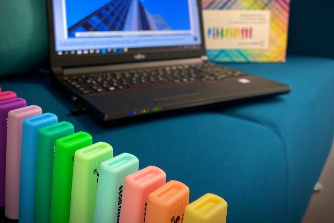 Es ist ein Laptop auf einer Sitzgelegenheit abgebildet, davor stehen mehrere bunte Textmarker.