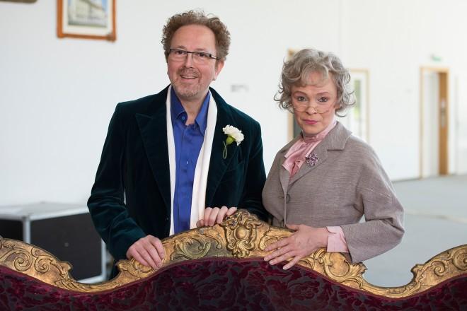 ein Mann und eine Frau stehen hinter einem Sofa