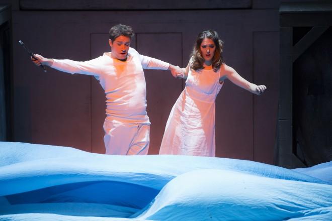 ein Mann und eine Frau stehen vor weißen Tüchern